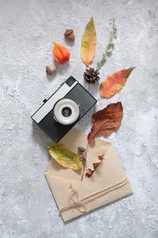Kompozycja jesień widok z góry. układ z rocznika aparatu, koperty i opadłych liści.