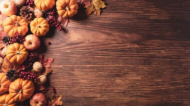 Kompozycja jesienna kwiaty bawełniane dyni i jesienne liście na ciemnym drewnie