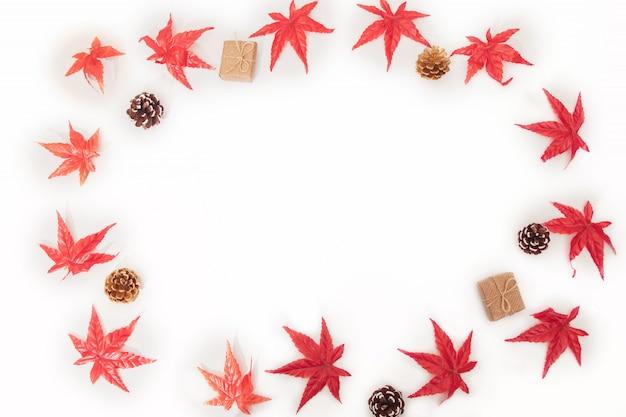 Kompozycja jesiennych liści klonu, kolorowe liście klonu, szyszki, pudełka na biały