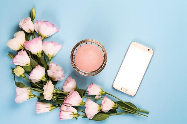 Kompozycja kadru kwiaty eustoma z telefonem i świecą leżały płasko. kwiatowe dekoracyjne rogi
