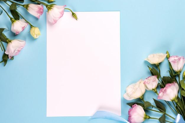 Kompozycja kadru z pustą przestrzenią w środku papieru wykonana z kwitnącego różowego eustoma, płasko ułożona. kwieciści dekoracyjni kąty na błękitnym tle.