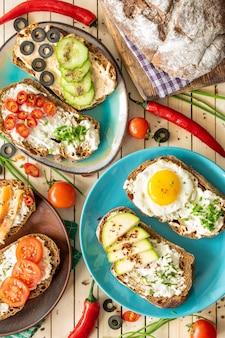 Kompozycja kanapek z warzywami łososiem i jajkiem na drewnianym tle prawidłowe odżywianie