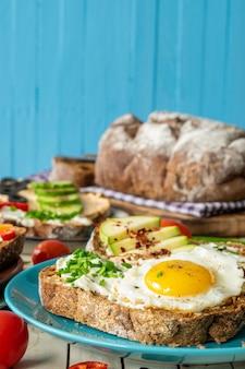Kompozycja kanapek z warzywami łososiem i jajkiem na drewnianym tle
