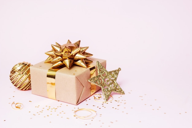 Kompozycja kartki świąteczne pozdrowienia. prezent papierowy ze złotą piłką, gwiazdą konfetti i złotą dekoracją na różowym tle