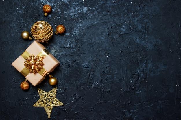 Kompozycja kartki świąteczne pozdrowienia. prezent ze złotą świąteczną dekoracją na ciemnym niebieskim tle.