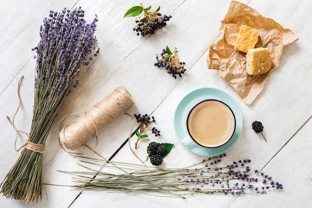 Kompozycja kawy, herbatników, jagód i kwiatów lawendy, widok z góry na białe drewno. niebieski kubek z kremową pianką