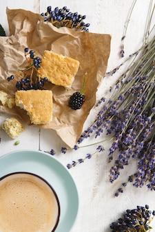 Kompozycja kawy, herbatników, jagód i kwiatów lawendy, zbliżenie na białym drewnie. niebieski kubek z kremową pianką