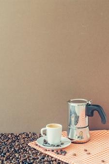 Kompozycja kawy z filiżanką i naczyniem moka na tkaninie
