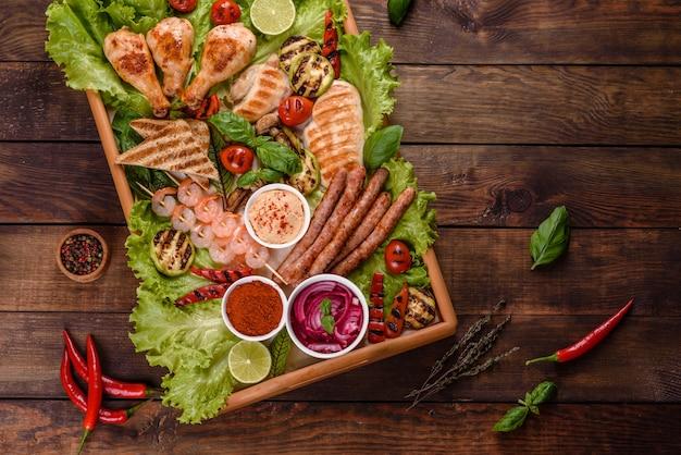 Kompozycja kiełbasek, kurczaka, wieprzowiny i krewetek przygotowanych na grillu, a także warzyw przygotowanych na grillu z przyprawami i ziołami. gotowanie na ogniu
