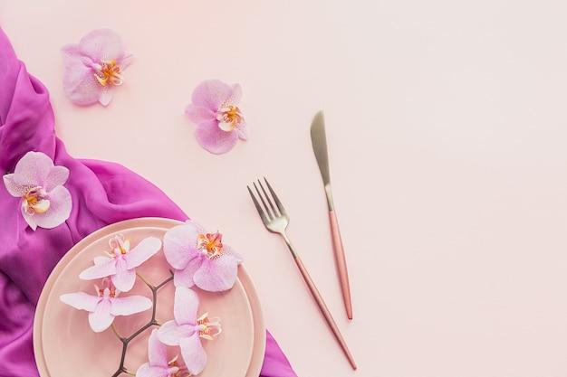 Kompozycja kwiatów i nakryć rozłożona płasko na jasnoróżowej powierzchni