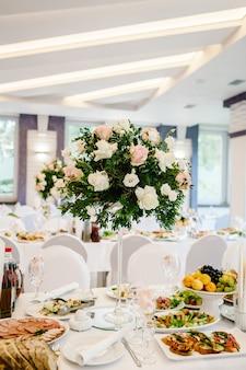Kompozycja kwiatów i zieleni znajduje się na świątecznym stole w sali weselnej. stoi świece. ścieśniać.