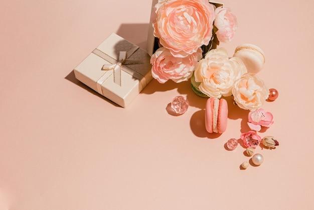 Kompozycja kwiatów, prezentów i makarunów w monochromatycznych brzoskwiniowych pastelowych kolorach. modna koncepcja minimalistyczna wiosna