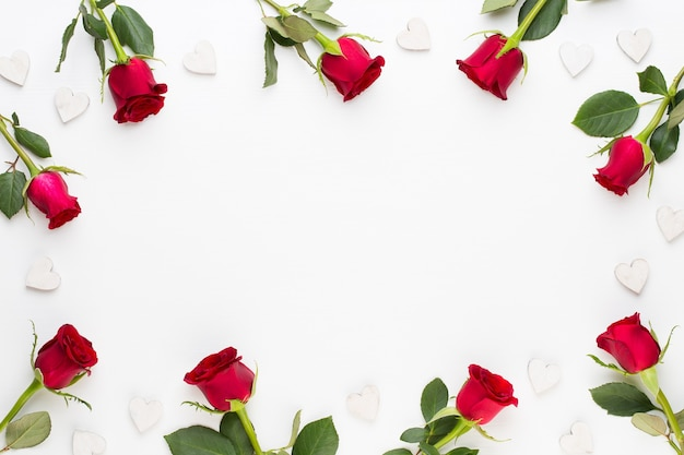 Kompozycja kwiatów. rama wykonana z czerwonej róży na białym tle. widok płaski, widok z góry.