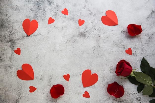 Kompozycja kwiatów. rama wykonana z kwiatów róży, konfetti na szarym tle. walentynki tło. leżał na płasko, widok z góry, miejsce na kopię.