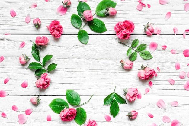 Kompozycja kwiatów rama wykonana ze świeżych kwiatów róży na białym tle drewnianych. leżał płasko. makieta