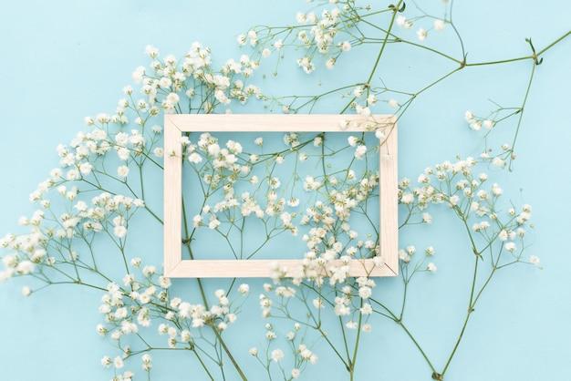 Kompozycja kwiatów romantyczna. białe kwiaty łyszczec, ramka na pastelowe niebieskie tło.