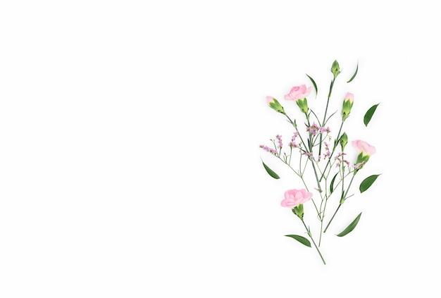 Kompozycja kwiatów. wzór wykonany z goździków, na białym tle leżał płaski, widok z góry, kwadrat.
