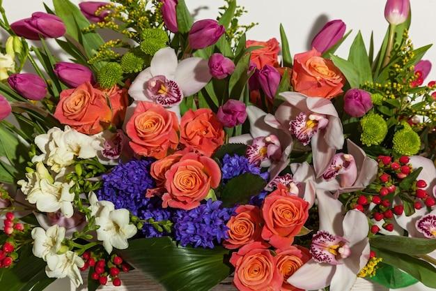 Kompozycja kwiatów z różowych róż, białych orchidei, czerwonych tulipanów, hiacynta i hrzemtem. kompozycja kwiatowa w pudełku dla dziewczynki róż, tulipanów i orchidei na białym tle