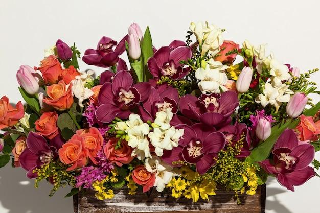 Kompozycja kwiatów z różowych róż, bordowych orchidei, czerwonych tulipanów, hiacyntów i hrzemtem. kompozycja kwiatowa w pudełku dla dziewczynki róż, tulipanów i orchidei na białym tle