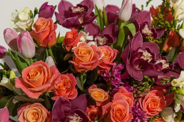 Kompozycja kwiatów z różowych róż bordowych storczyków czerwonych tulipanów hiacynta i hrzemtem f