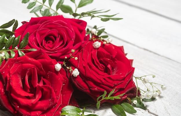 Kompozycja kwiatowa czerwonych róż z bliska na drewnianym białym stole