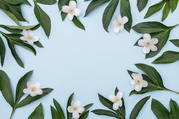 Kompozycja kwiatowa rama kwiatów i zielonych liści na niebieskim tle,