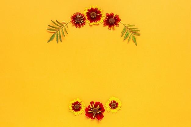 Kompozycja kwiatowa. rama kwiatowy okrągły wieniec żółtych czerwonych kwiatów na pomarańczowym tle