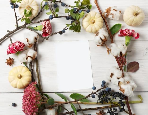 Kompozycja kwiatowa. rama wykonana z suszonych jesiennych kwiatów, dyni, gałęzi i jesiennych liści, również bawełny, goździków i tarniny. widok z góry