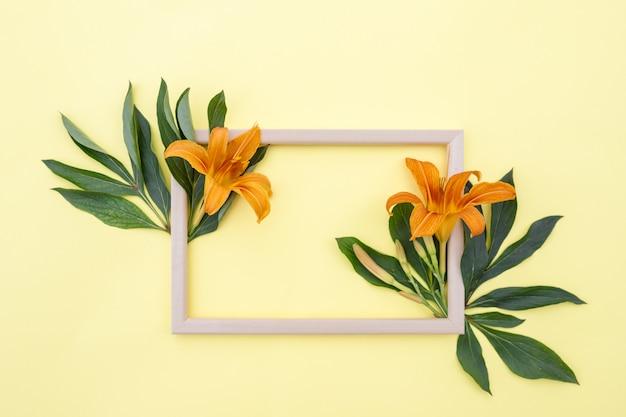 Kompozycja kwiatowa rama żółto-pomarańczowe kwiaty lilii i zielonych liści na żółtym tle
