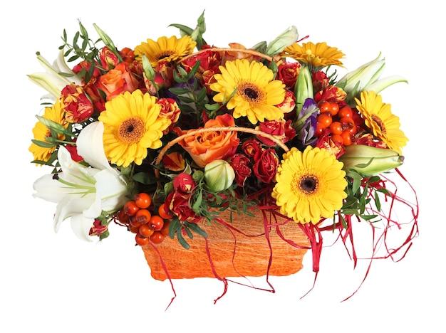 Kompozycja kwiatowa w pomarańczowy kosz, róże, żółte stokrotki gerbera i białe lilie, na białym tle.
