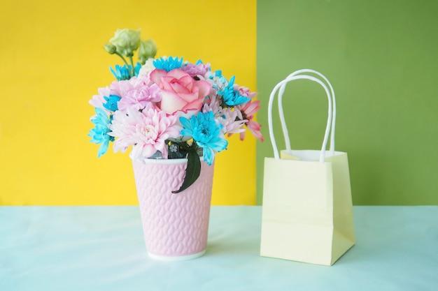 Kompozycja kwiatowa w różowym kubku i papierowej torbie na wielobarwnym jasnym tle.