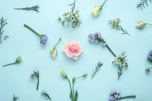 Kompozycja kwiatowa widok z góry, kwiatostany róża, eustoma, limonium na niebieskim tle, płaska leżanka