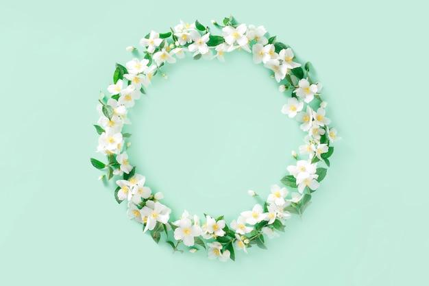 Kompozycja kwiatowa wieniec z białych wiosennych kwiatów jaśminu na pastelowej zieleni