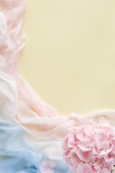 Kompozycja kwiatowa wykonana z różowych kwiatów i pastelowego szalika. leżał płasko, widok z góry, miejsce