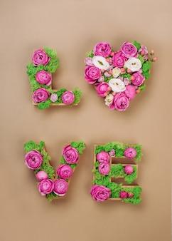 Kompozycja kwiatowa z literami love słowo ze stabilizowanym mchem i różami na tle papieru rzemieślniczego. widok z góry, płaski układ.