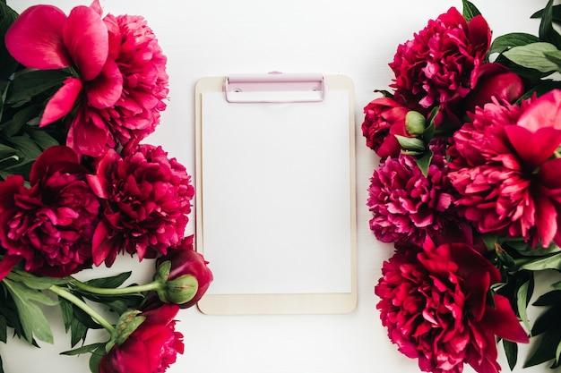 Kompozycja kwiatowa z ramą kwiaty czerwonej piwonii i schowka na białym tle. płaski układanie, widok z góry