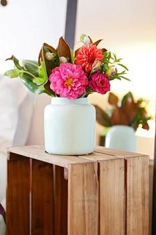 Kompozycja kwiatowa z różowych kwiatów w białym wazonie ceramicznym na drewnianym pudełku