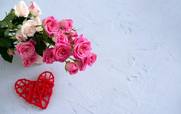 Kompozycja kwiatowa z różowymi różami i czerwonym sercem na szaro. koncepcja walentynki