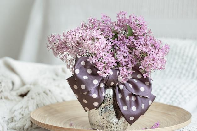 Kompozycja kwiatowa ze świeżymi kwiatami bzu i kokardą jako detalem dekoracyjnym