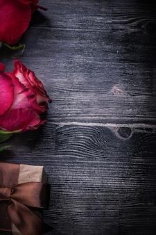 Kompozycja kwitnących pachnących pąk róży pakowane pudełko na drewniane tła