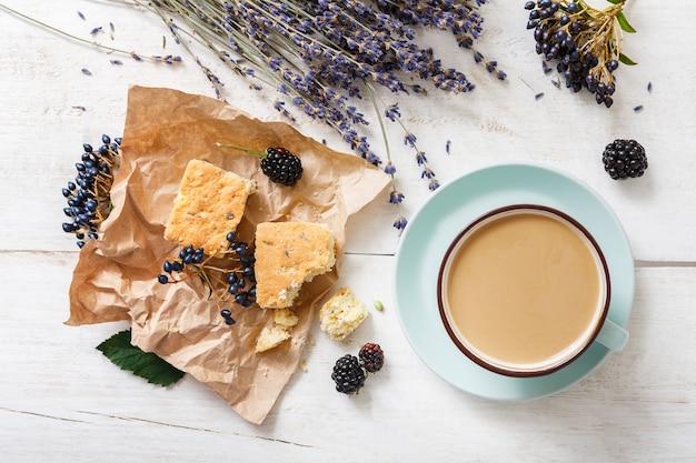Kompozycja latte, herbatników, jagód i kwiatów. niebieska filiżanka kawy z kremową pianką, suszonymi kwiatami, ciasteczkami i jeżyną na białym drewnianym stole, widok z góry. gorące napoje, koncepcja oferty sezonowej