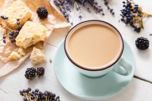 Kompozycja latte, herbatników, jagód i kwiatów. niebieska filiżanka z kremową pianką, suszonymi kwiatami, ciasteczkami i jeżyną przy białym drewnianym stole. gorące napoje, koncepcja oferty sezonowej