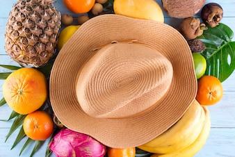 Kompozycja letnia. Tropikalni palma liście, kapelusz, wiele owoc na błękitnym drewnianym tle.