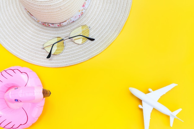 Kompozycja letniej plaży. minimalne proste mieszkanie leżało z płaską czapką okulary przeciwsłoneczne i nadmuchiwany flaming na białym tle na żółtym tle. podróż wakacje koncepcja podróży przygoda. widok z góry