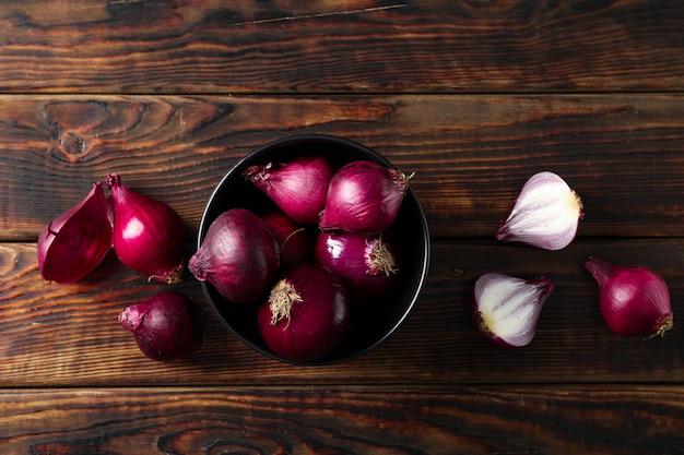 Kompozycja leżąca na płasko z czerwoną cebulą na drewnianym