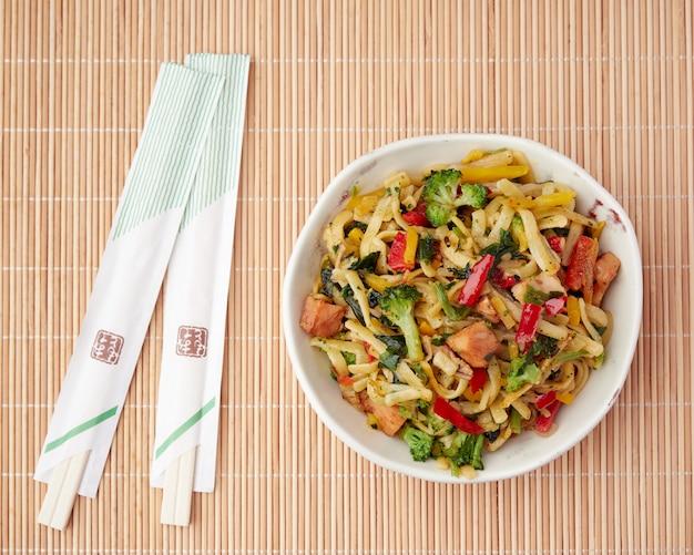 Kompozycja leżąca płasko na bambusowej macie z orientalnym jedzeniem w misce, makaronem i warzywami oraz pałeczkami