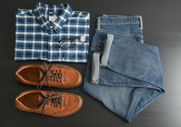 Kompozycja leżąca płasko z dżinsami, koszulą, okularami i butami na czarnym stole