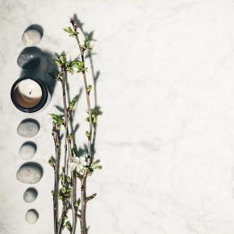 Kompozycja leżąca płasko z pięknymi wiosennymi gałęziami wiśni, naturalną świecą i szarymi kamieniami na białym tle z marmuru.