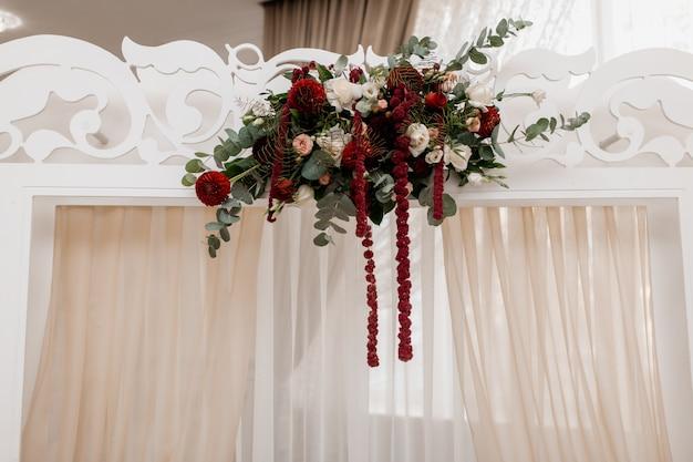 Kompozycja na białym łuku ślubnym wykonana z kwiatów eukaliptusa i bordo