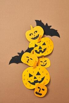 Kompozycja na halloween rękodzieło z papieru z przerażających dyń i nietoperza na brązowym tle z miejscem na tekst. połóż się na flay